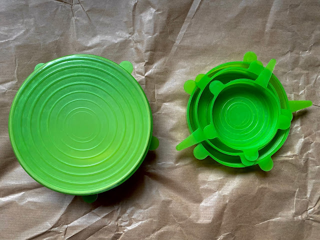 a multi pack of stretchy green silicone bowl covers including one stretched over a bowl.
