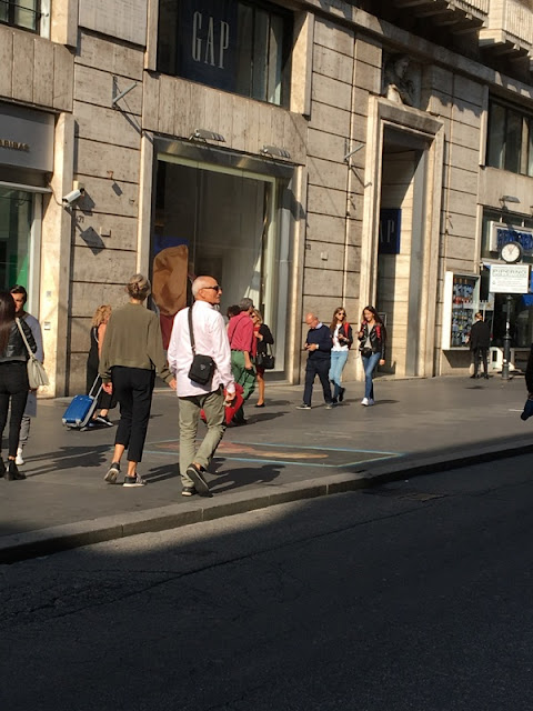 couple strolling down a street in Rome