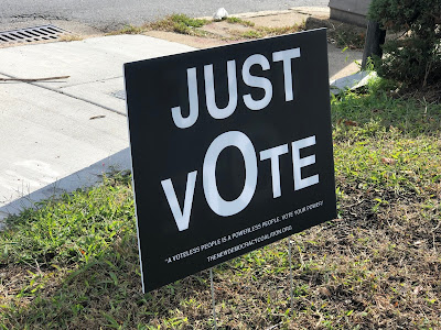 """Black sign on lawn, white text: """"Just Vote."""" Smaller text: """"A Voiceless people is a powerless people. Vote your power."""""""