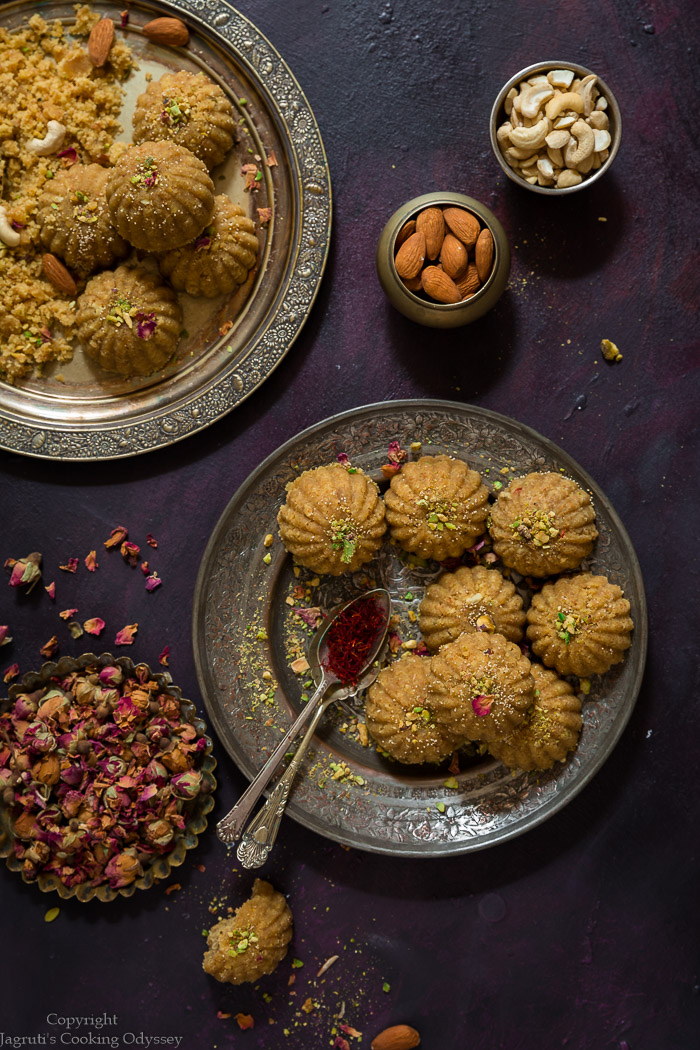 Microwave churma ladwa garnished with almond and pistachio slivers and saffron threads in rustic metal plate with a bowl of dried rose buds.