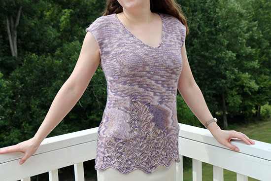 Front view of a woman standing in front of a white rail and green trees wearing a lavender colored sleeveless hand knit top with a lace motif toward the lower hem.