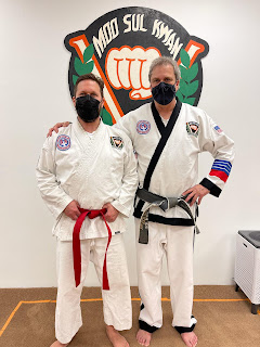 A martial arts black belt master instructor standing with adult taekwondo student recently promoted to red belt