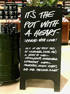 A black rectangular board that says its the pot with a heart in white font on a bright background