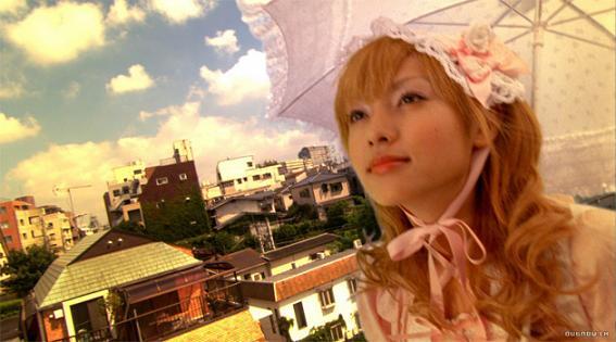 fotograma de la película japonesa Conociendo a Matsuko, donde la chica muestra un vestido rosa con sombrilla del mismo color y de fondo la ciudad en un plano oblicuo