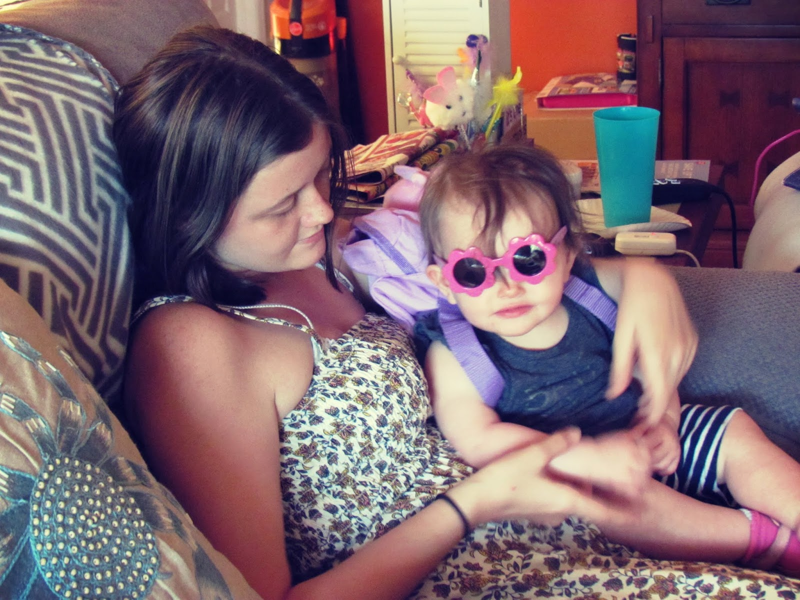 An aunt and niece lay together with baby girl in sunglasses smiling on her birthday