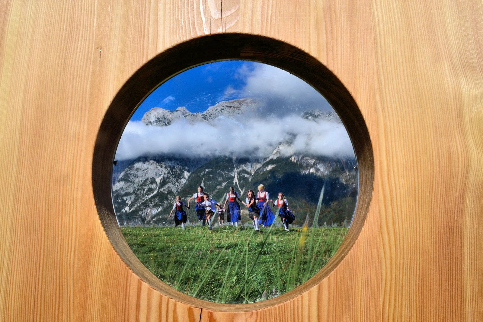 This clever sign welcomes you to the Sound of Music Trail. Look carefully and you'll see that the bottom half of this circular window (figures and grass in foreground) is actually a painting while the top half allows you to view the stunning background through clear glass.