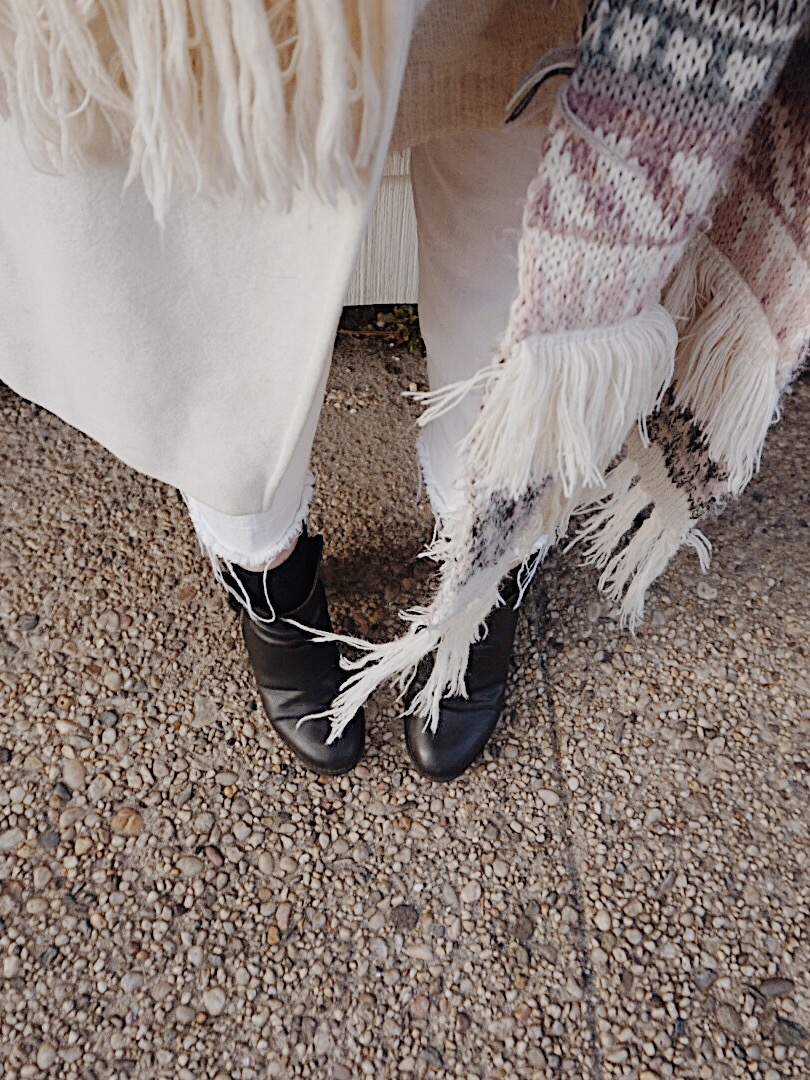 a close up image of black boots and a winter scarf
