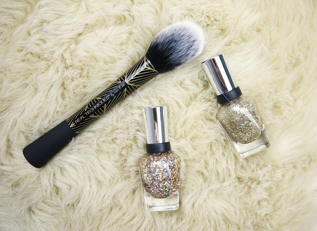 a real techniques black blush brush with gold detail, and two gold glitter nail polishes on a cream faux fur background