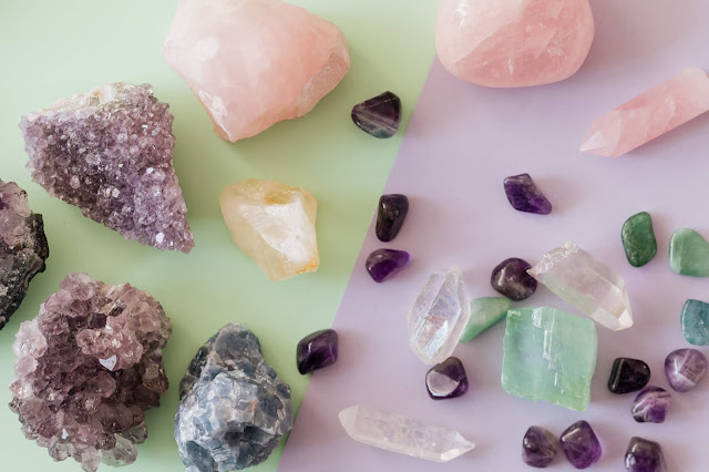 A variety of crystals displayed against a green and lavender pastel background.