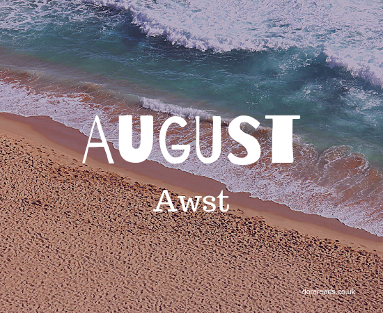 August - Awst title graphic with a seaside/beach background