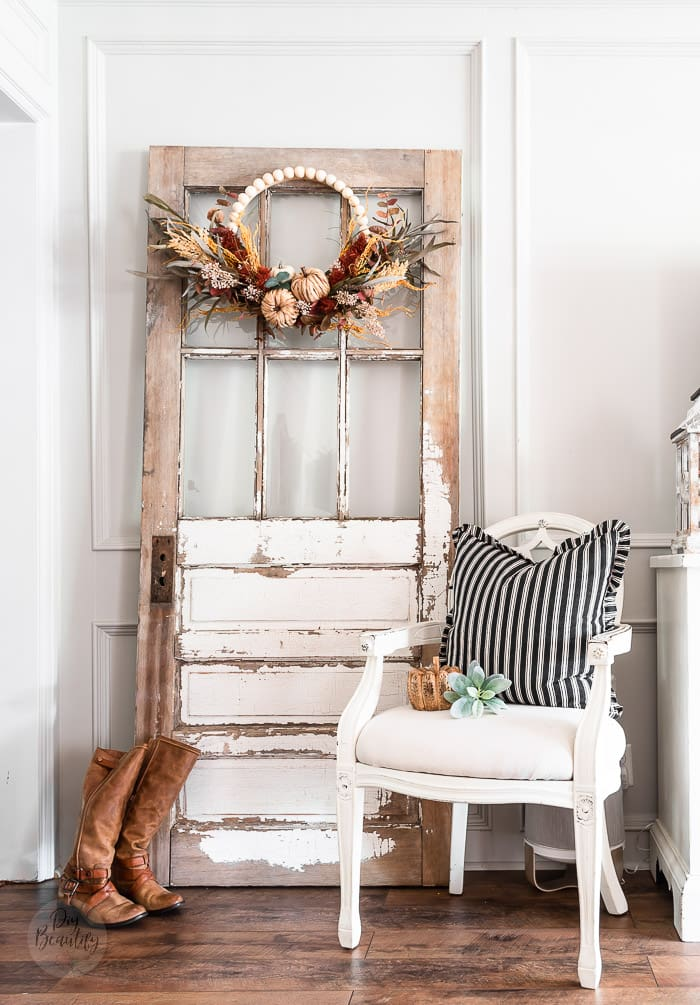 Fall wreath on chippy old door, leather boots, white chair with black and white pillow