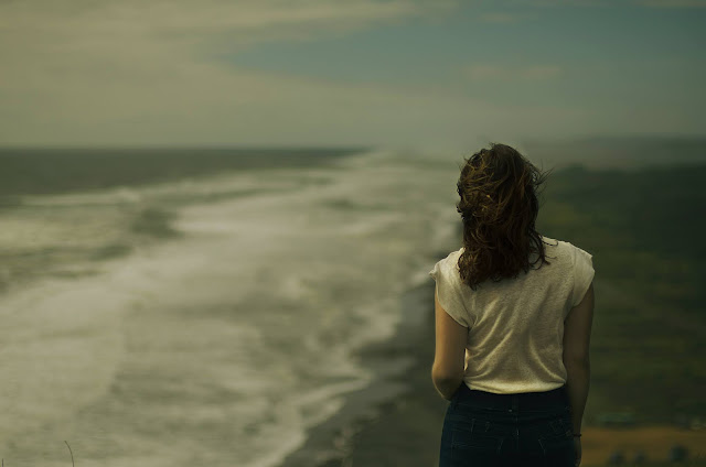 A woman looking into the distance at the beach