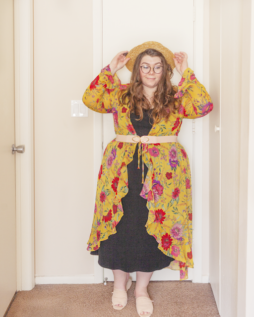 An outfit consisting of a straw boater hat, a semi sheer long sleeve yellow floral robe with bell sleeves and ruffles, belted with a pink belt over a black a-line midi dress and pink slides.