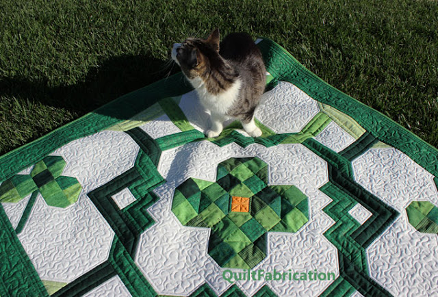 cat sitting on a green clover chain quilt