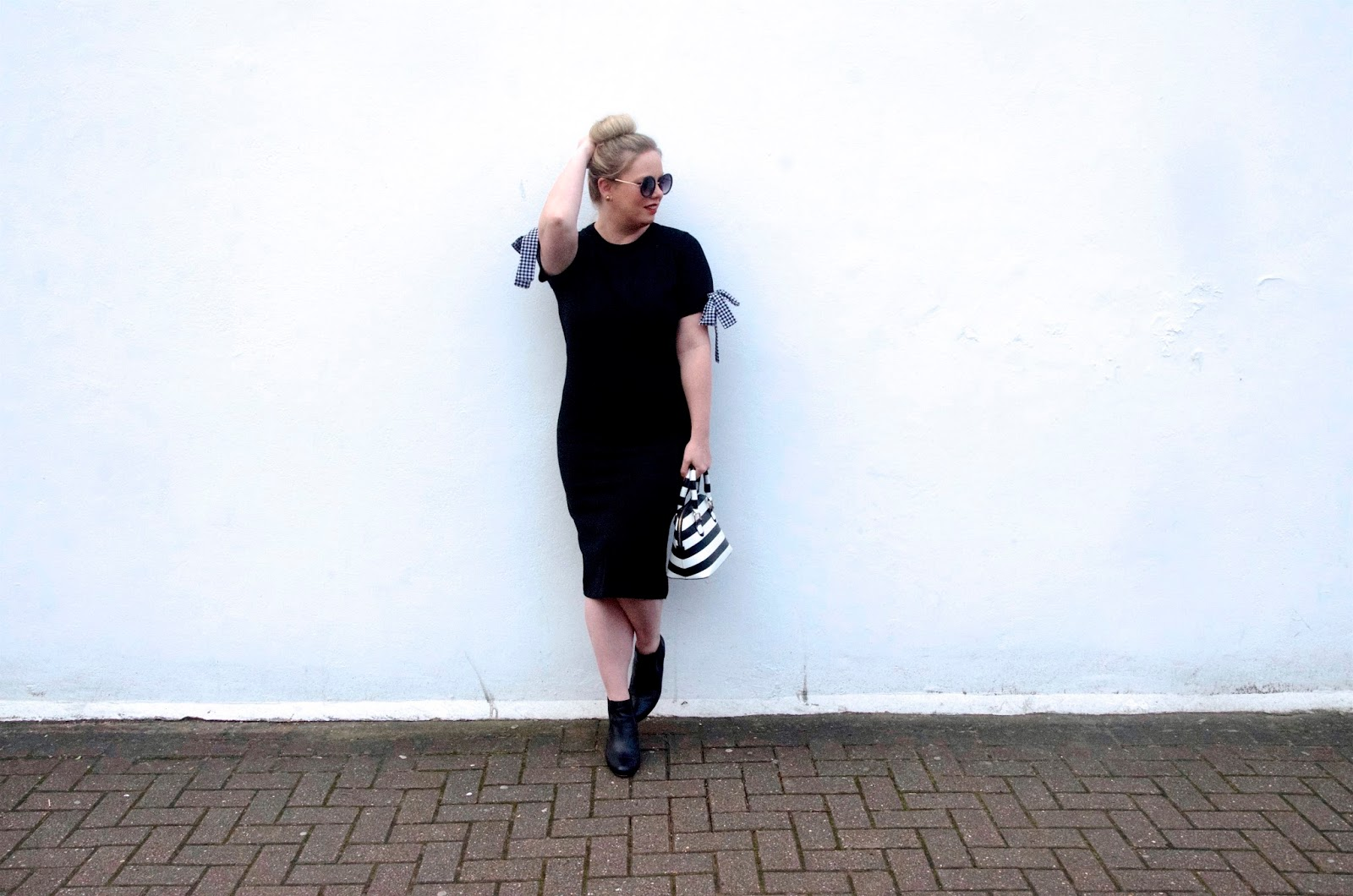black midi dress with gingham bow sleeves, ankle booties and striped bag