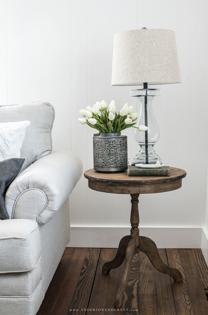 Wood side table holding white tulips beside sofa.