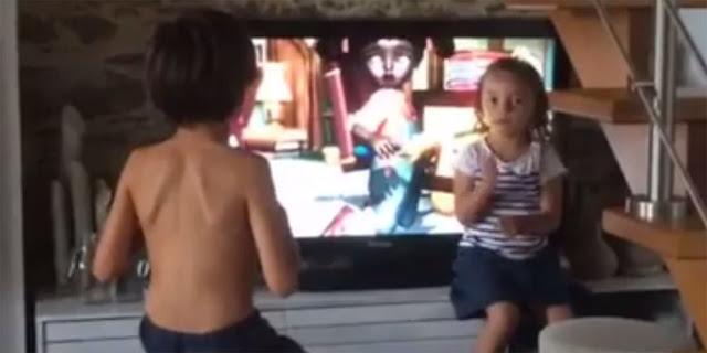 Niña interpretando de televisión a a lengua de signos a su hermano sordo