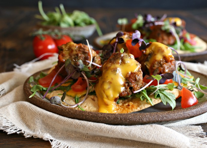 Recipe for meatballs flavored with taco seasonings such as cumin, chili powder and oregano. Served on tortillas.