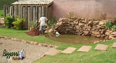 Construção do lago com as paredes de pedra onde vamos colocar a bica d'água de madeira para o monjolo de madeira funcionar. Na foto fazendo o buraco onde vamos colocar o pau para instalar o eixo de madeira do monjolo.