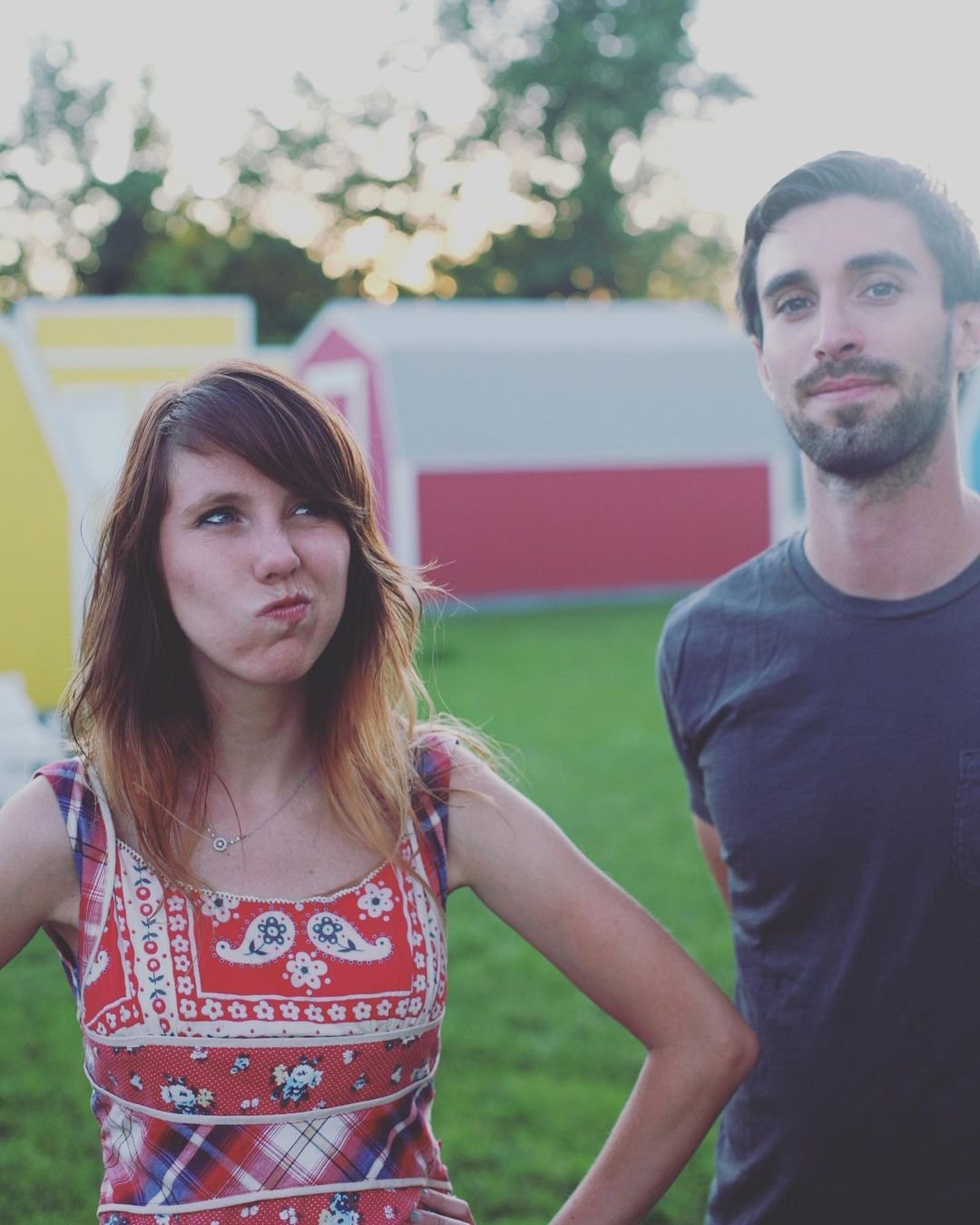 Suzie with a crooked smile and Jesse poses in front of a unfocused yard with red and yellow house shapes and grass