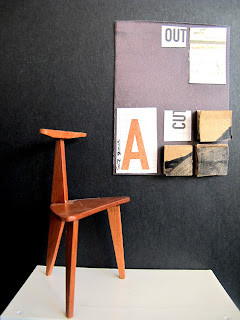 Modern dolls' house miniature collage art work hanging on a black wall. In front of it is an art chair.