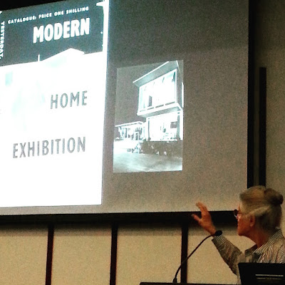 Mary Featherston giving a talk in front of a slide showing a flier of the Modern Home Exhibition.