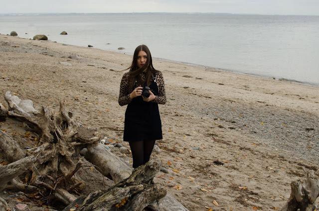 Lea am Strand mit einer Kamera in der Hand, sie sieht nachdenklich aus.