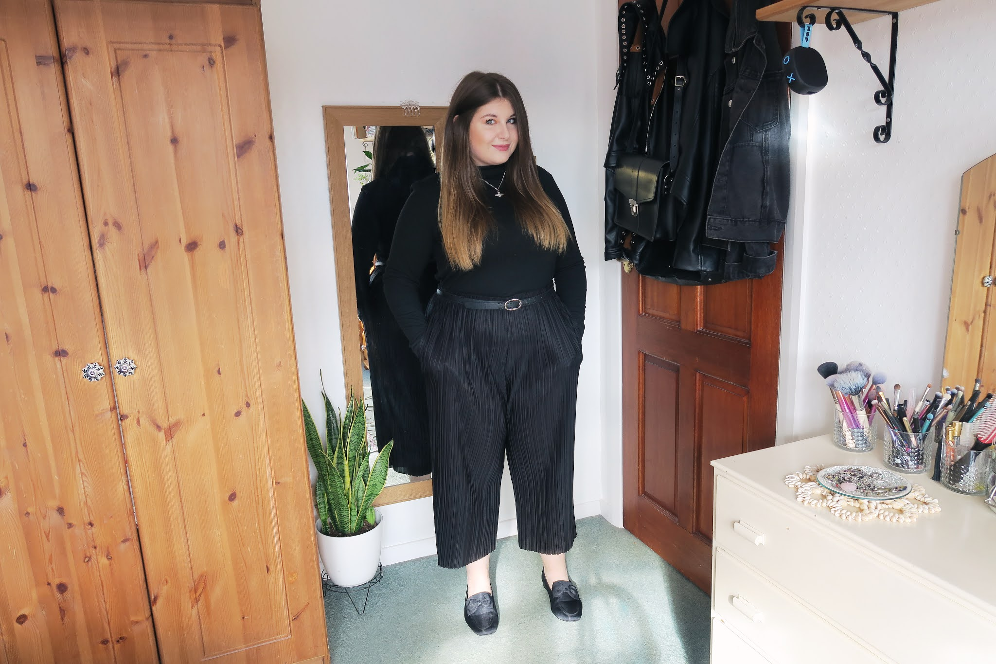 Grace is wearing a black roll neck top tucked into a pair of plain black culottes. On her feet she is wearing a pair of plain black loafers