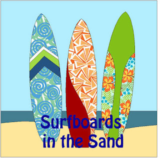 three different colorful surfboards standing up in the sand with an ocean behind