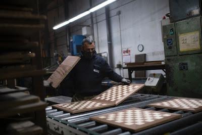 Un employé de l'usine Rechapados Ferrer vérifie la finition des échiquiers le 5 mars 2021 à La Garriga, près de Barcelone - Photo © AFP/Josep Lago