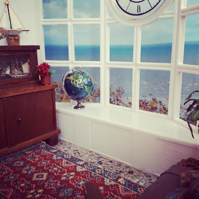 1/12 scale miniature living room scene with an antique cupboard, afghan rug and sea chest. The windows have a view over the sea, and on the windowsill stands a globe.