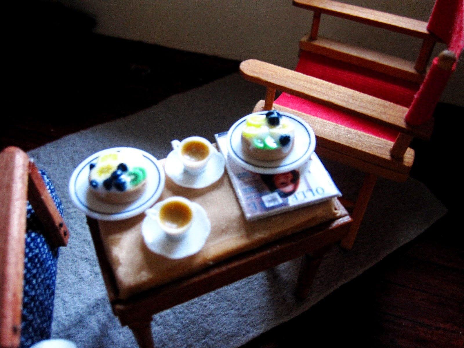 Aerial view of a miniature holiday house scene showing a sitting area with a 1950s-style lounge chair and directors chair . Between them is a piano stool set with two flans on plates and two cups of tea on top.