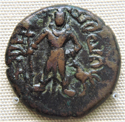 Kartikeya holding a spear / scepter with a cockerel to his left.