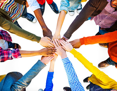 image of a group of people standing in a circle with hands joined in the center.
