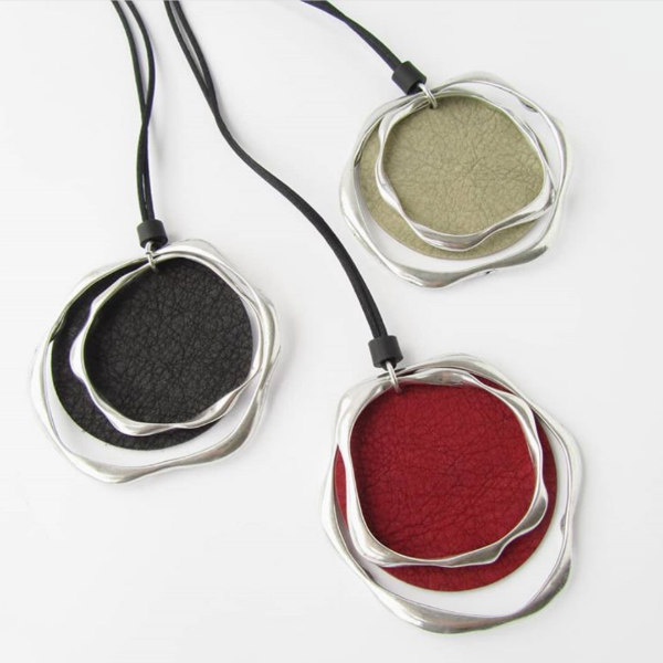 trio of circular paper and aluminum pendants on black cording