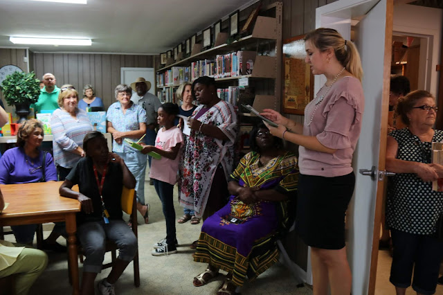 A woman addresses groups of people standing around the inside of a library.