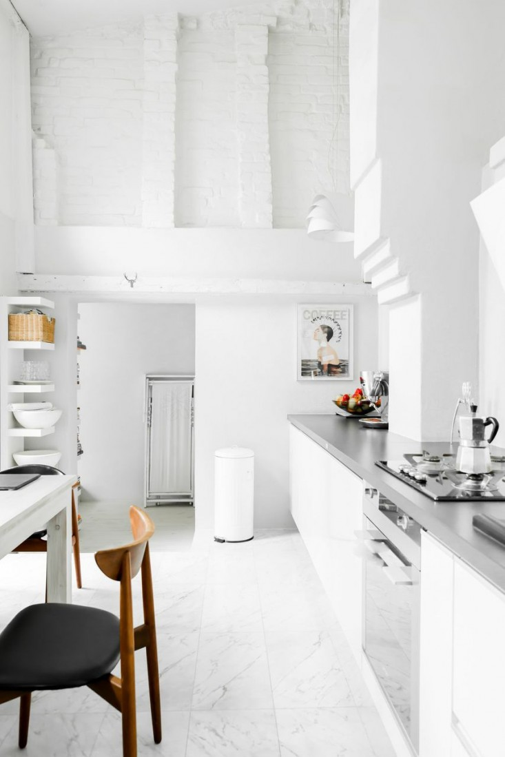 Cocina blanca con sillas de madera y asientos negro