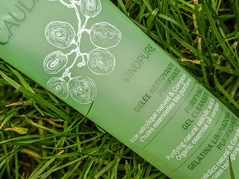 a close up of Caudalie Vinopure Purifying Gel Cleanser in a green tube with a white illustration of grapes