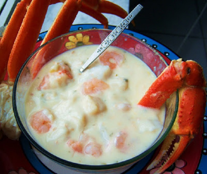 this is a bowl of delicious crab legs, shrimp and other seafood all in a big glass bowl called chowder. This seafood medley of chowder is rich and delicious often made at Christmas eve as a special Holiday  treat