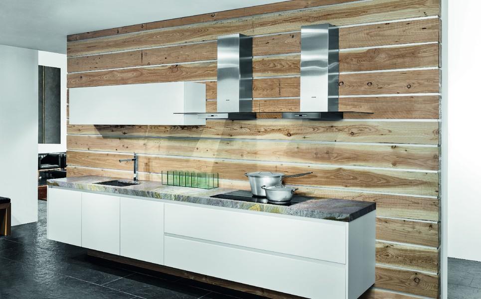 el acabado de la pared de esta cocina es lo que le da el toque particular con grandes caceroleros y campana decorativa doble para personas que les guste