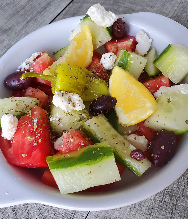 this is a bowl of Greek Salad with homemade greek salad dressing on top