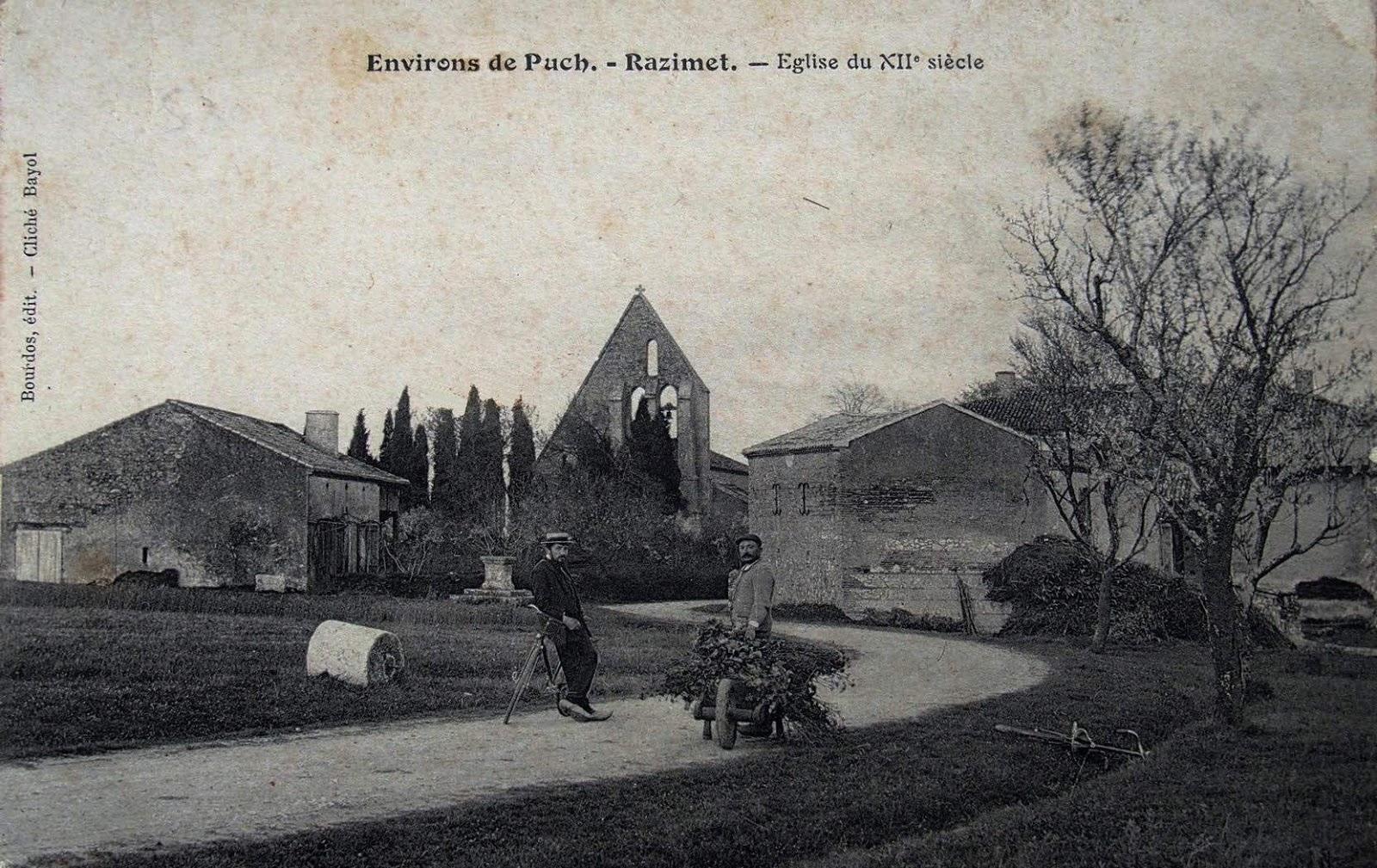 carte postale ancienne de l'entrée bourg de Razimet, l'instituteur appuyé sur son vélo devise avec le paysan devantysa brouette, en fond l'église