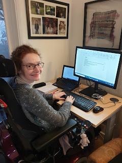 Hannah sitting in her powerchair under a desk with a laptop, monitor, keyboard and mouse on it. She is smiling at the camera.