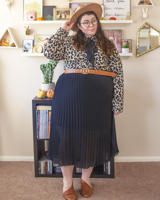 An outfit consisting of camel brown wide brim fedora, a light brown leopard print long sleeved blouse with an attached black pussy bow tucked into a black pleated midi skirt and brown d'orsay flats.