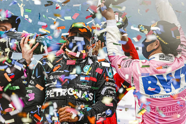 Sebastian Vettel, Ferrari, 3rd position, and Sergio Perez, Racing Point, 2nd position, pour Champagne down the back of Lewis Hamilton, Mercedes-AMG Petronas F1, 1st position, on the podium