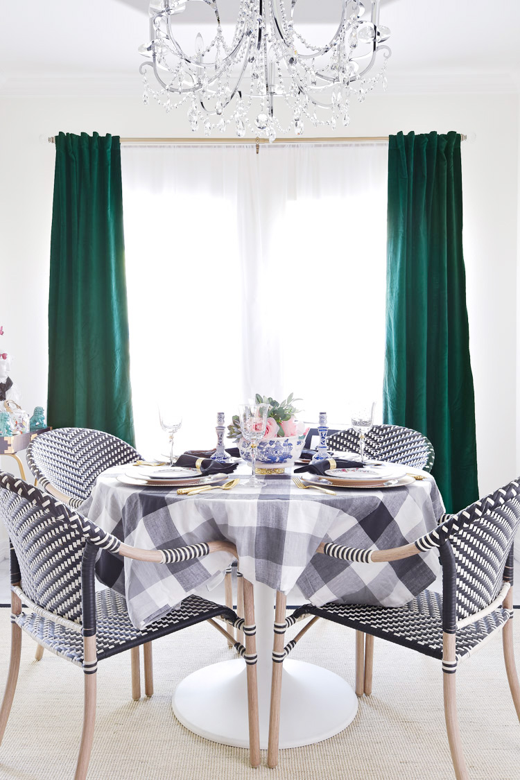 A black and white small dining room with green and emerald velvet curtains. Love the fall tablescape with chinoserie dinnerware.