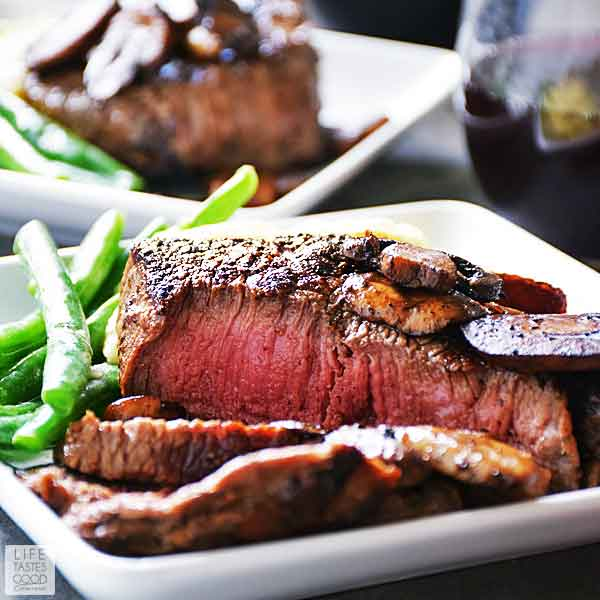 Pan seared sirloin steak dinner for two with sauteed mushrooms, mashed potatoes, & steamed green beans on a white plate