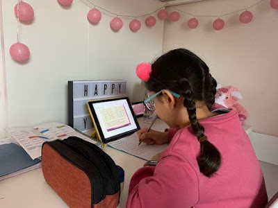 Child learning from home on an iPad at a desk