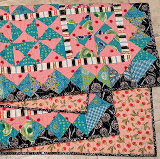 Folded quilt shows front, back, and binding of Hourglass 2 quilt