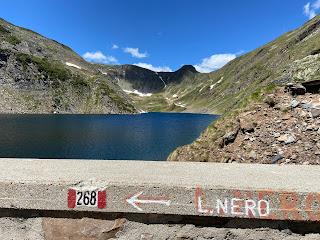 The dam at Lago di Aviasco with trail indicators.